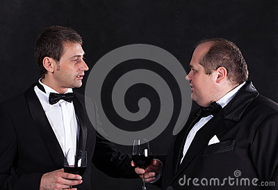 Two stylish businessman in tuxedos with glasses of red wine