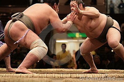 Two sumo wrestlers engaging in a fight Editorial Stock Photo