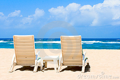 Two sun beach chairs on coast near ocean