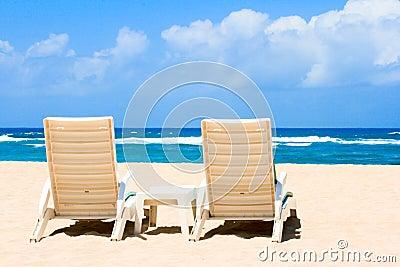 Two sun beach chairs on coast near ocean