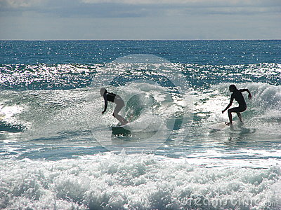 Two surfers riding a wave. Editorial Stock Photo