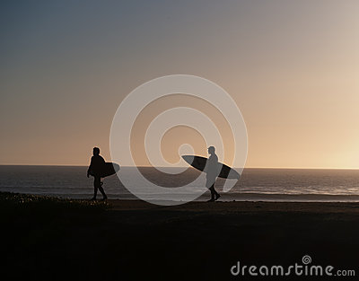 Two surfers walking towards the waves in the sunset