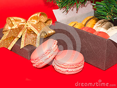 Two sweet macarons against Gift box