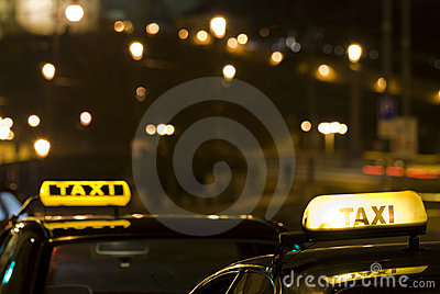 Two taxi signs at night