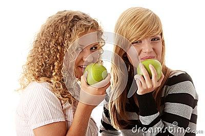 Two teen girlfriends eating green apples