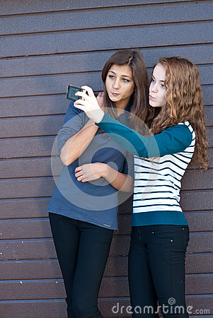 Two teen girls taking picture of themselves using tablet pc