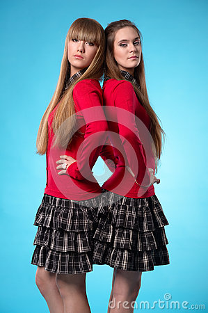 Two teen schoolgirls stand back to back over blue background