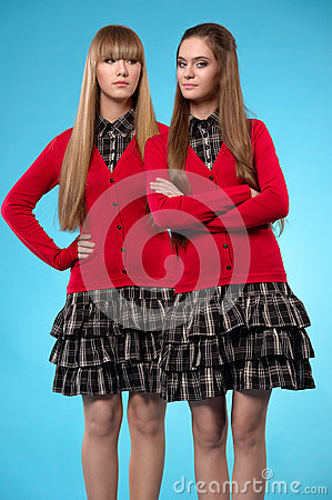 Two teen schoolgirls stand side by side over blue background