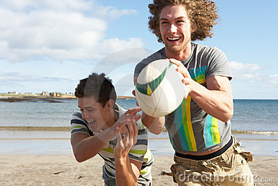 Two Teenage Boys Playing Rugby On Beach