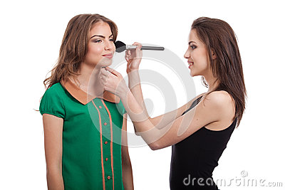 Two teenage girls applying blush