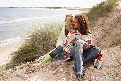 Two Teenage Girls Sitting In Sand Dunes