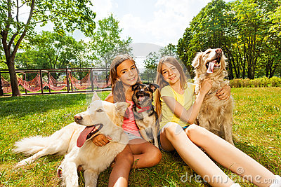 Two teenage girls sitting with three dogs in park stock for Dog day sitting
