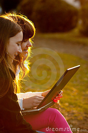 Two teenage girls working on notebook in the park