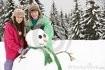 Two Teenagers Building Snowman On Ski Holiday