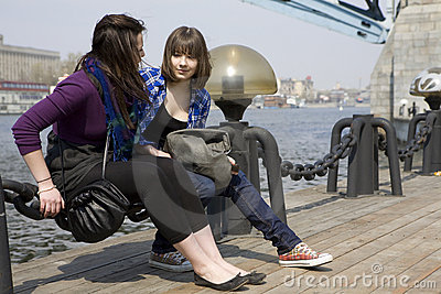 Two teens girl sitting on embankment.