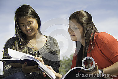 Two teens or young women studying