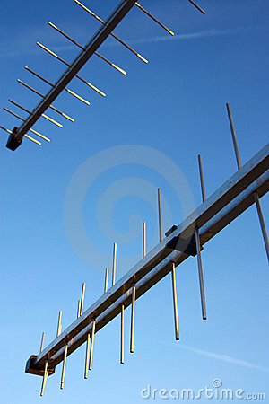 Two television antennas under blue sky