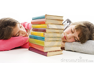 Two tired teenage girls with pile colored book