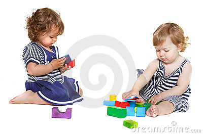 Two toddler girls playing with building blocks