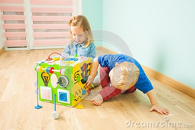 Two toddlers sitting on a floor near large toy Stock Photo