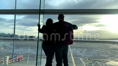 Two tourists, a man and a woman with a backpack, are standing in the airport lounge, looking out the window, travel concept stock video footage