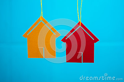 Two toy houses with blue blurred background