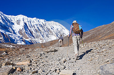 Two trekkers running on the road against Tilicho