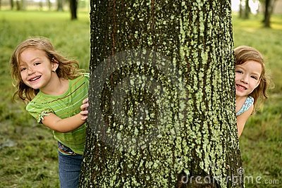 Two twin little girls playing in tree trunk