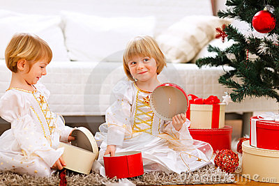 Two twins girl opening gifts near Christmas tree