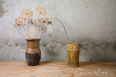 Two vases with dry colours on a  table