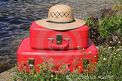 Two vintage red suitcases and sun hat