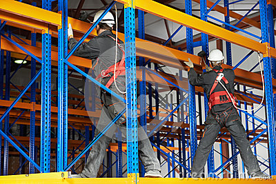 Two warehouse workers installing rack arrangement