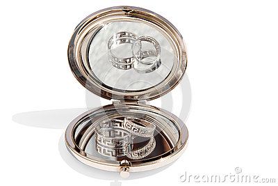 Two wedding gold rings in a small round glass mirror