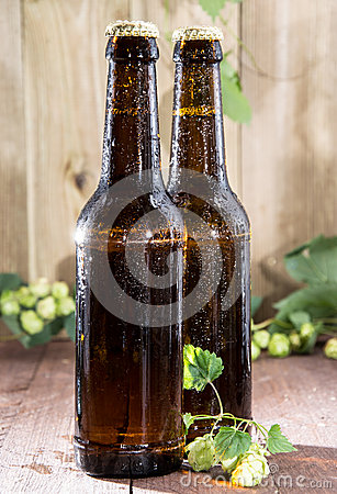 Two wet bottles of Beer on wood
