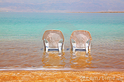 Two white beach chairs stood side by side