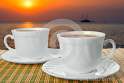 Two white cups with saucer