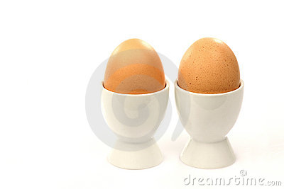 Two white egg cups with brown eggs