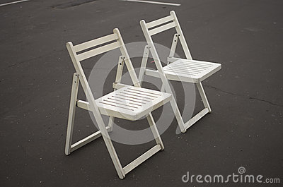 Two white folding chairs