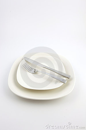 Two white plates and a knife and fork