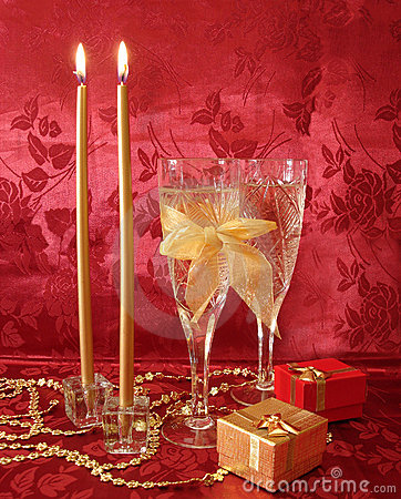 Two wine glasses with champagne, gifts and golden candles on red