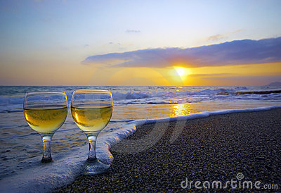 Two wineglasses on the sand and sunset