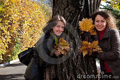 Two woman with bouquets of maple leaves near tree