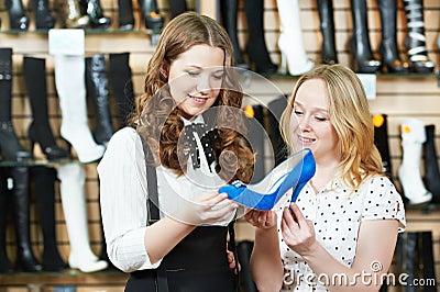 Two woman choosing shoes in footwear store