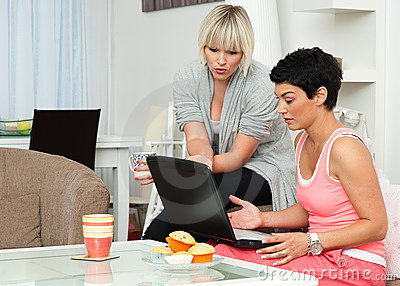 Two woman friends with laptop at home