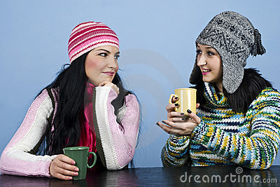 Two women discuss and enjoy a hot drink