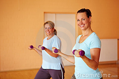 Two women doing dumbbell exercises