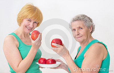 Two women eating an apples