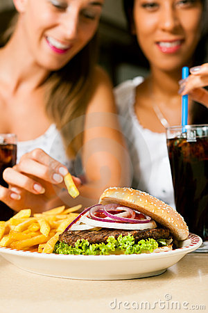 Two women eating hamburger and drinking soda