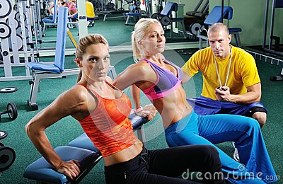 Two women exercise with personal fitness trainer