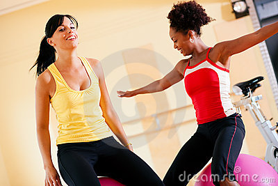 Two women with fitness ball in gym
